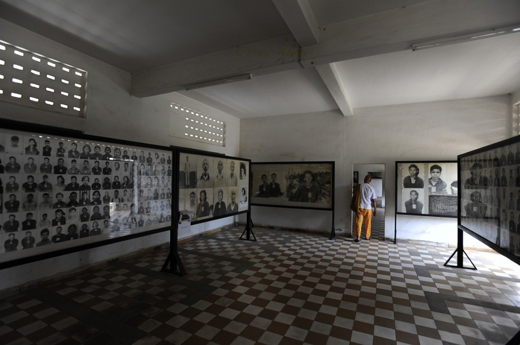A visitor moves from room to room observing the displays of countless photos of men, women, and children tortured and murdered at  S-21 prison.