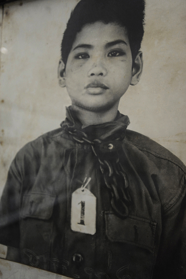 A young boy wearing tag No1. He was the first person to be tortured and murdered at S-21.